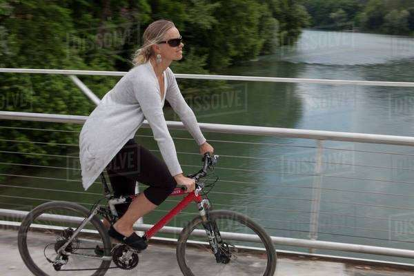 Woman biking on a bridge in Piedmont, Italy Royalty-free stock photo