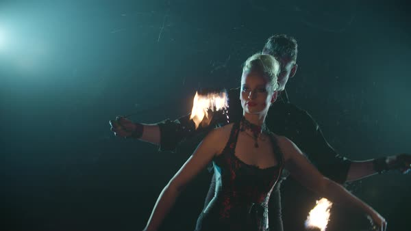 Male and female performers spinning fire poi during their stage performance Royalty-free stock video