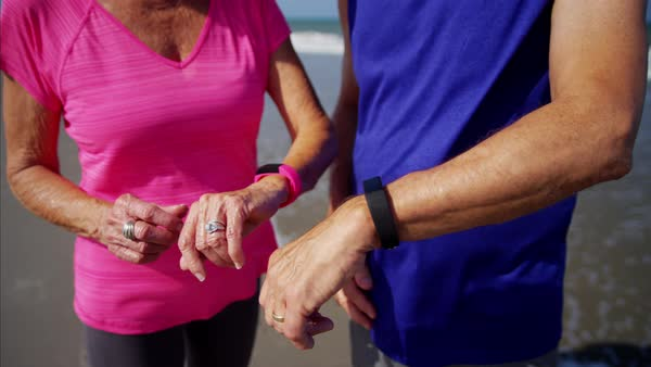 Senior couple wearing sport watches on the ocean beach Royalty-free stock video