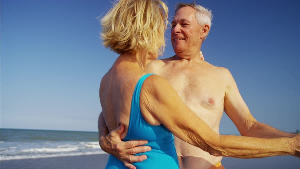 Smiling mature couple in swimsuits dancing on the beach Royalty-free stock video