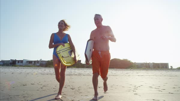 Mature couple in swimsuits running with body boards on the beach Royalty-free stock video