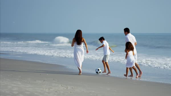 Happy children enjoying vacation with parents playing with ball on beach Royalty-free stock video