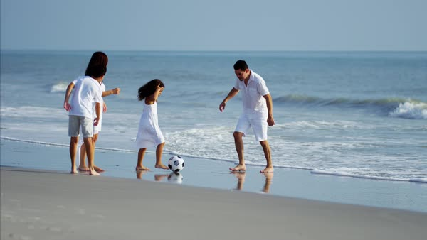 Parents enjoying holiday with children playing with ball on the beach Royalty-free stock video