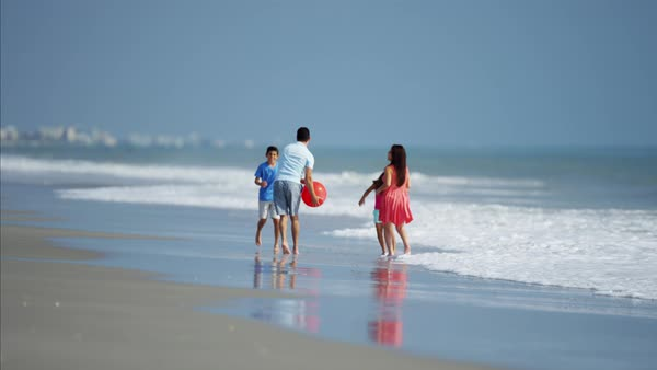 Parents enjoying holiday with children playing with red ball on beach Royalty-free stock video