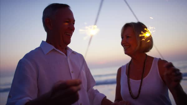 Mature Caucasian couple having fun with sparklers on ocean beach at sunset Royalty-free stock video
