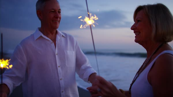 Mature Caucasian couple having fun with sparklers on the beach at sunset Royalty-free stock video