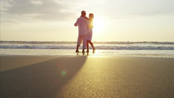 Silhouette of mature Caucasian couple dancing on the beach at sunset Royalty-free stock video