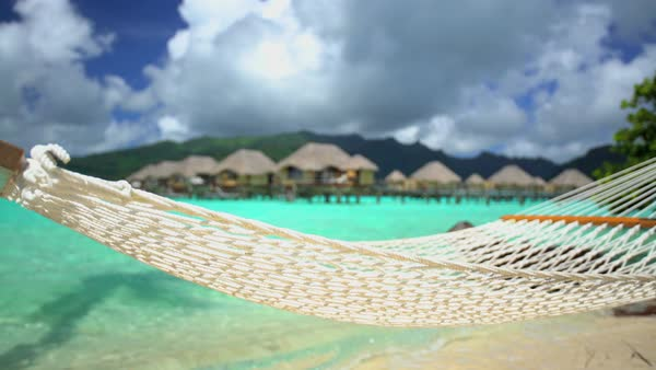 Beach hammock Overwater Bungalows in tropical aquamarine lagoon a luxury vacation resort in Bora Bora South Pacific French Polynesia Royalty-free stock video