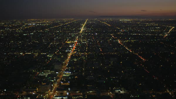 Aerial cityscape view of vehicle traffic showing grid system in illuminated city suburbs at dusk Los Angeles California USA Royalty-free stock video