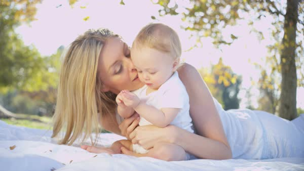 Loving beautiful blonde Caucasian mother chilling outdoors on the blanket kissing her young child Royalty-free stock video