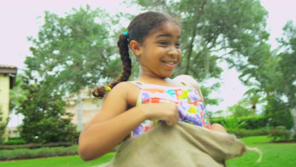 Portrait of cute African American girl taking part in fun sports events with friends in home garden  Royalty-free stock video