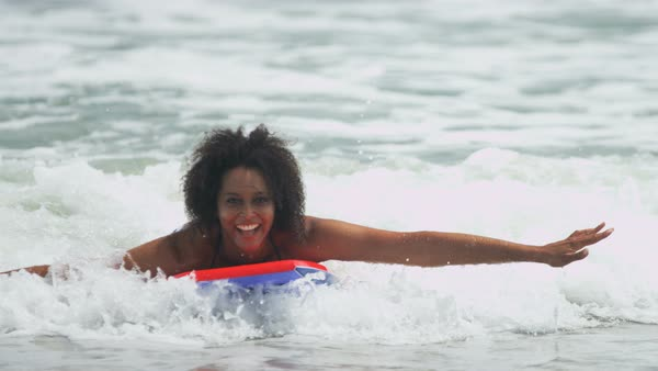 Portrait of happy ethnic female with afro hair in swimwear on bodyboard enjoying the waves Royalty-free stock video