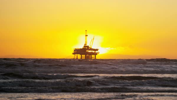 Silhouette of Oil rig coastal platform at sunset drilling for fuel Pacific coastline slow motion California USA  Royalty-free stock video
