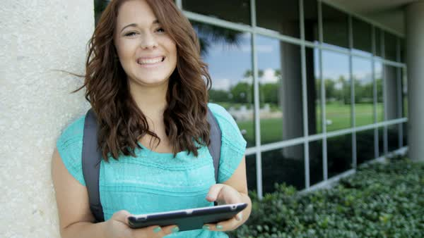 Portrait of young Caucasian American female student holding wireless touchscreen technology at front of college campus outdoors Royalty-free stock video