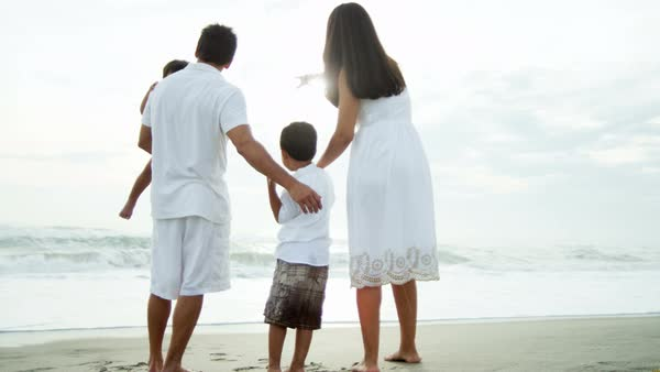 Young Hispanic family enjoying freedom and the waves at the beach on vacation Royalty-free stock video