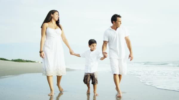 Carefree Hispanic parents enjoying the water by the ocean holding hands with their child Royalty-free stock video