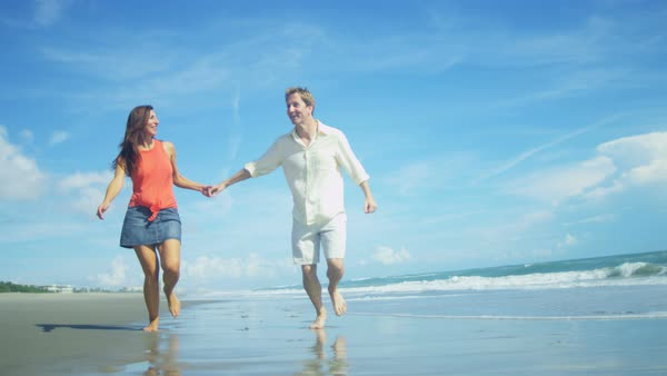 Carefree beautiful Caucasian couple running for fun on the beach in the shallows at a coastal resort Royalty-free stock video
