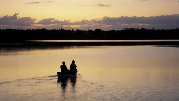 Silhouette of retired Caucasian American couple enjoying the sunset having kayaking trip on the lake outdoors Royalty-free stock video