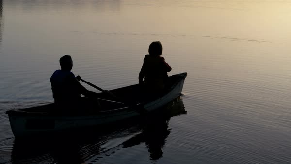 Silhouette of healthy senior Caucasian American couple outdoors in the boat on the lake paddling and enjoying the sunrise  Royalty-free stock video