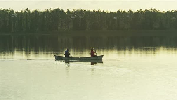 Mature Caucasian American couple enjoying the sunset having canoeing trip on the lake Royalty-free stock video