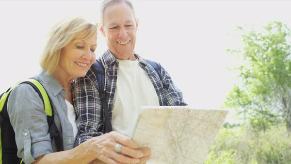Healthy senior Caucasian American couple wearing casual clothing reading map enjoying their lifestyle outdoors  Royalty-free stock video