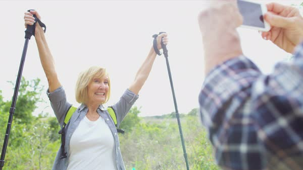 Mature Caucasian American couple having fun with mobile taking picture on hike in the nature  Royalty-free stock video