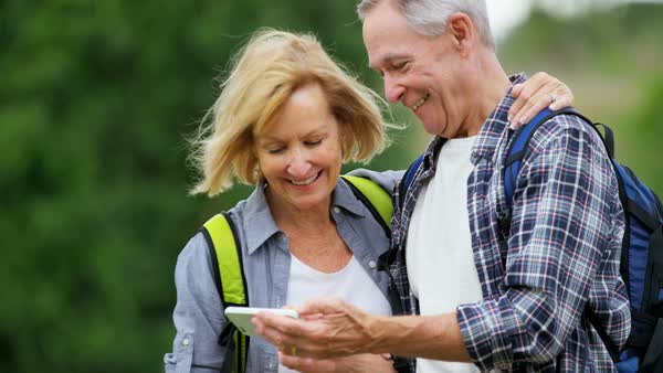 Happy retired Caucasian American couple watching picture on mobile enjoying their vacation hiking outdoors Royalty-free stock video