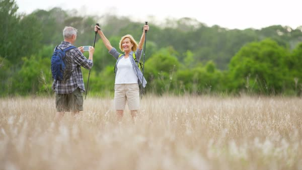 Happy retired Caucasian American couple having fun with smartphone taking photo on hike in the park outdoors Royalty-free stock video