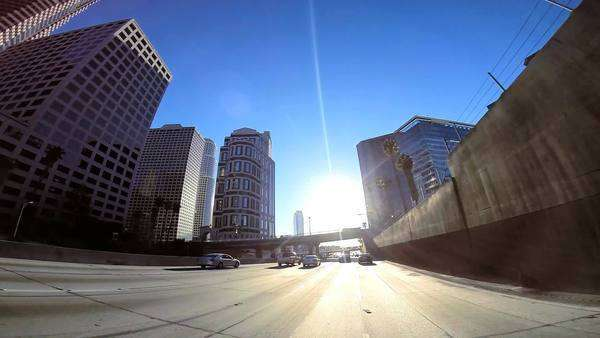 POV wide angle city skyscrapers vehicle traffic Los Angeles USA sun flare Royalty-free stock video