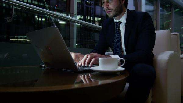 Close-up shot of businessman using laptop and drinking coffee Royalty-free stock video