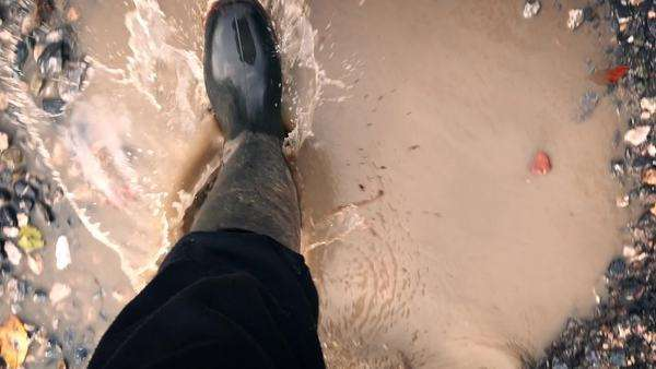 POV of legs with boots on walking through puddles and gravel Royalty-free stock video