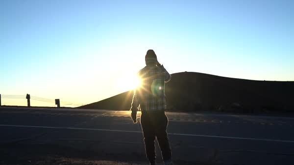 Medium shot of a man walking on a road at sunset Royalty-free stock video