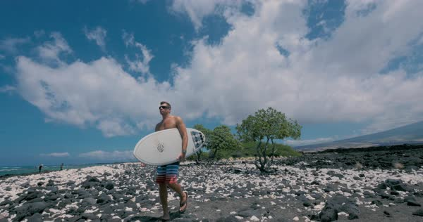Wide shot of a man walking on a beach with a surfboard Royalty-free stock video