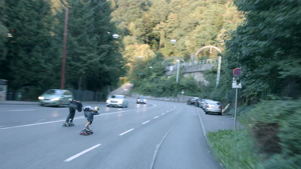 A dolly shot of two skateboarders as they speed down a street in Stuttgart Royalty-free stock video