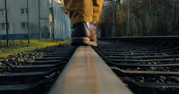 A man walks on a railway line away from the camera Royalty-free stock video