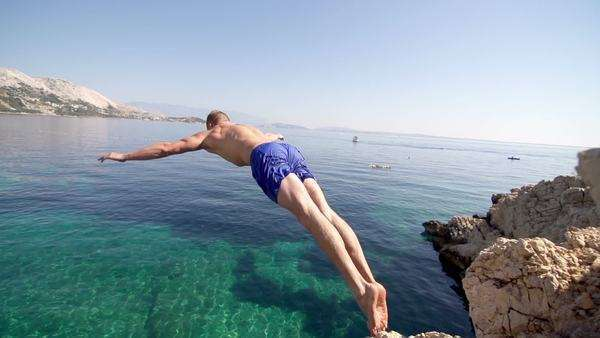 Spectacular slow motion of a muscular young man jumping off the cliff into clear blue water with arms outstretched Royalty-free stock video