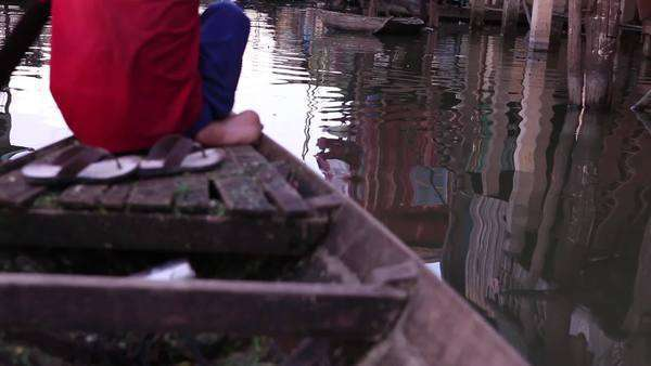 Handheld shot in a paddling boat showing the water surface reflecting traditional stilt houses Royalty-free stock video