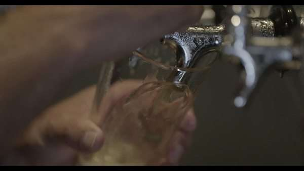 Handheld shot showing a beer tap filling a glass in slow motion Royalty-free stock video