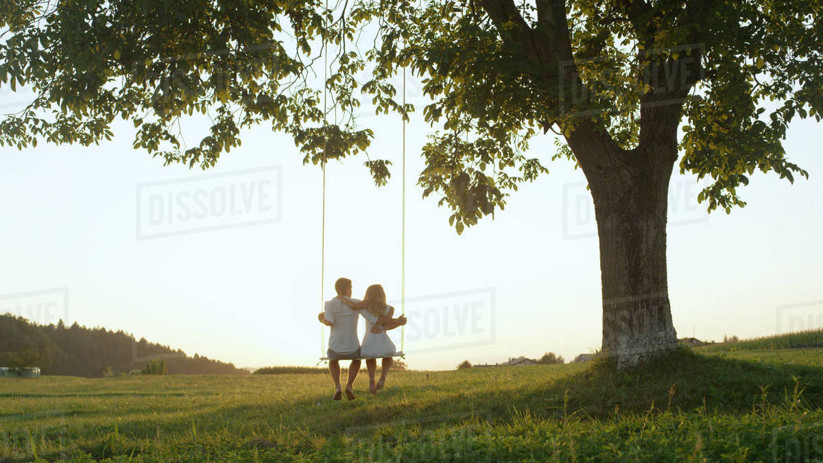 Setting sun shining over young couple's shoulders on rope swing. Young adults on romantic summer date, leaning back embraced on swing under tree and watching the golden sunset Royalty-free stock photo