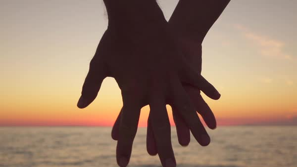 People holding hands across sunset ocean Royalty-free stock video