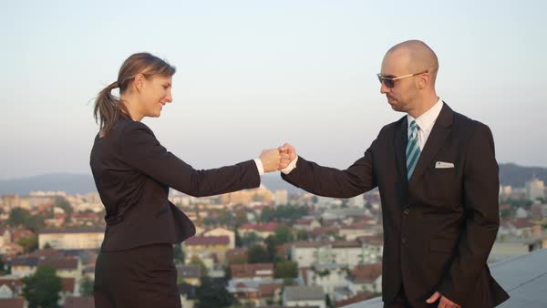SLOW MOTION CLOSE UP DOF: Businessman successfully accomplishing commercial deal bumping fists with female representative of corporate financial company on top of office building with stunning view Royalty-free stock video