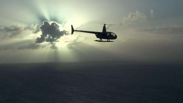 Handheld shot of a helicopter flying in a sky with bright sunlight passing through the clouds Rights-managed stock video