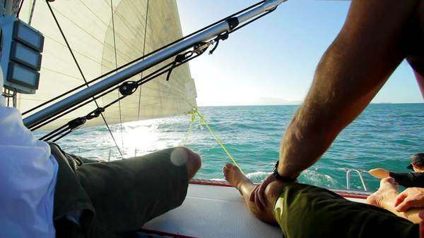 Handheld shot on a sailing boat showing marine scenery and people relaxing Rights-managed stock video
