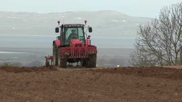 Medium wide shot of tractor approaching Rights-managed stock video