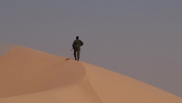 Wide shot of a soldier walking on a dune Rights-managed stock video