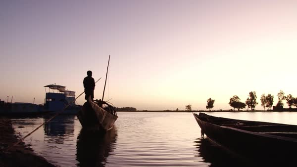 Wide shot of a child paddling on a boat in Mali Rights-managed stock video