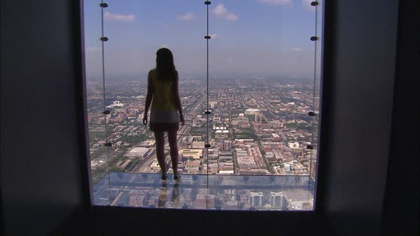 Wide shot of a woman viewing the city from a glass balcony Rights-managed stock video