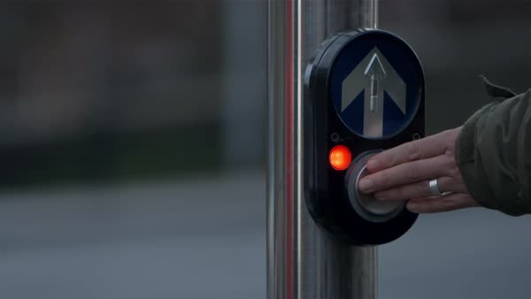 Close up shot of a person pushing a button of a pedestrian signal Rights-managed stock video