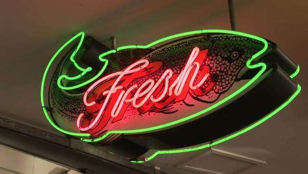 Bright neon fish shaped sign reading fresh, Pike Street Market, Seattle, Washington, zoom out Royalty-free stock video