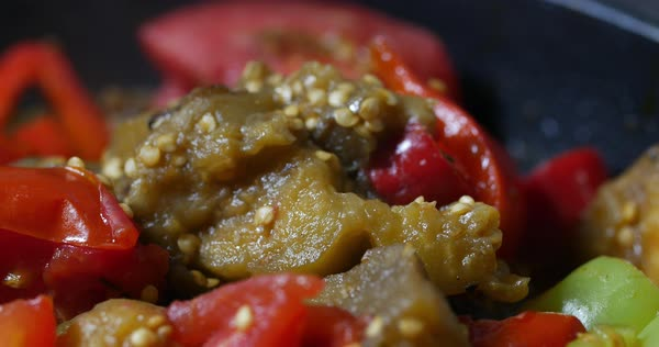 Extreme close up vegetable ragout being quenched in saucepan with red and green paprika zucchini and tomato Royalty-free stock video